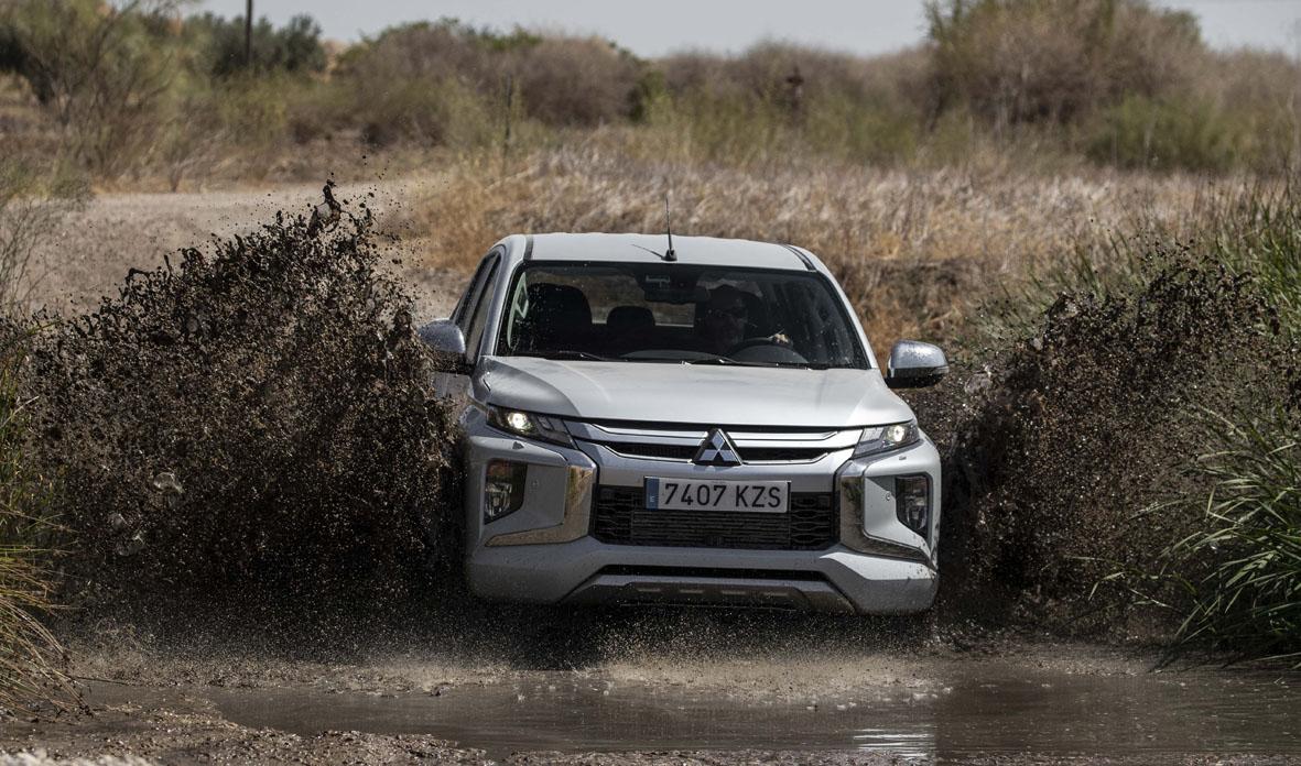 Aspecto frontal del nuevo Mitsubishi L200 atravesando una poza de barro y agua.